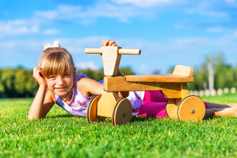 Little girld and runbike on the grass meadow. Little girld with wooden runbike laying on on the grass meadow in summer stock image