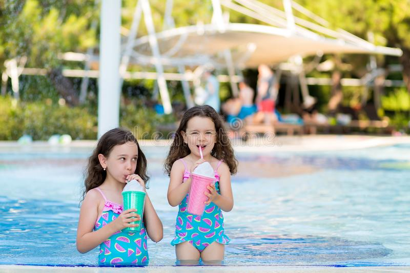 Little girls in bright swimsuits drink cocktails near the pool on a Sunny summer day stock photo