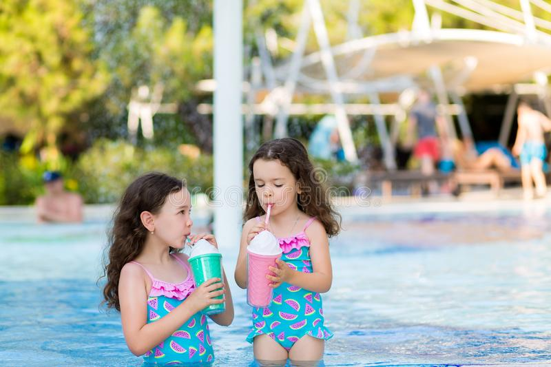 Little girls in bright swimsuits drink cocktails near the pool on a Sunny summer day stock photos