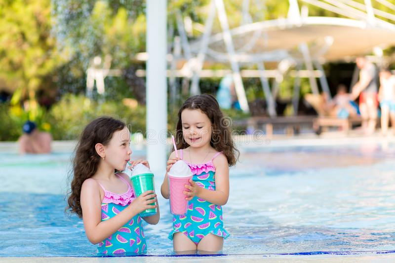 Little girls in bright swimsuits drink cocktails near the pool on a Sunny summer day stock images