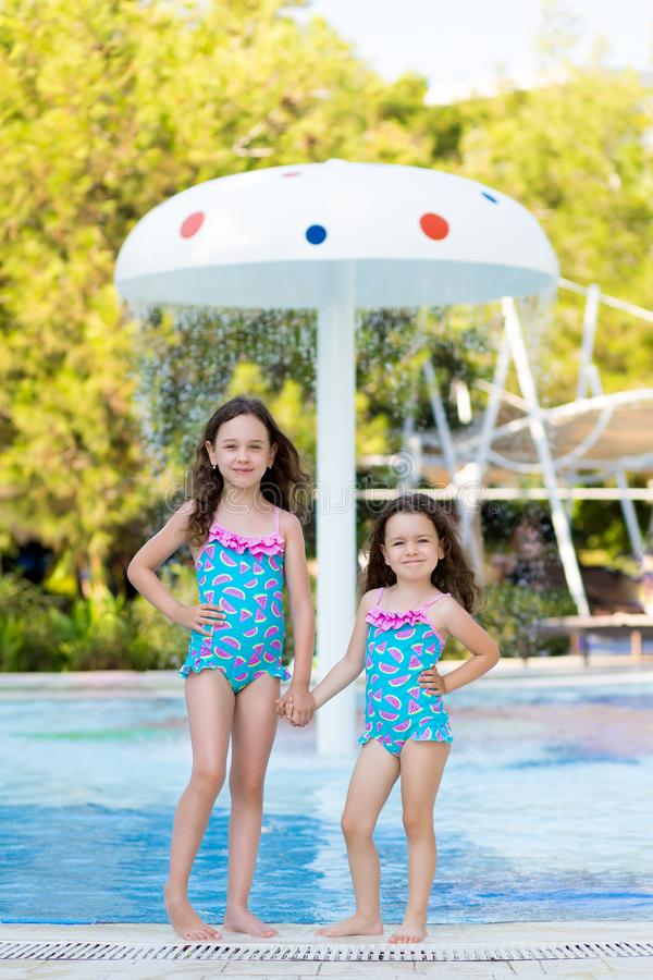 Little girls in bright swimsuits posing near the pool on a Sunny summer day on background of fountain umbrella stock photo