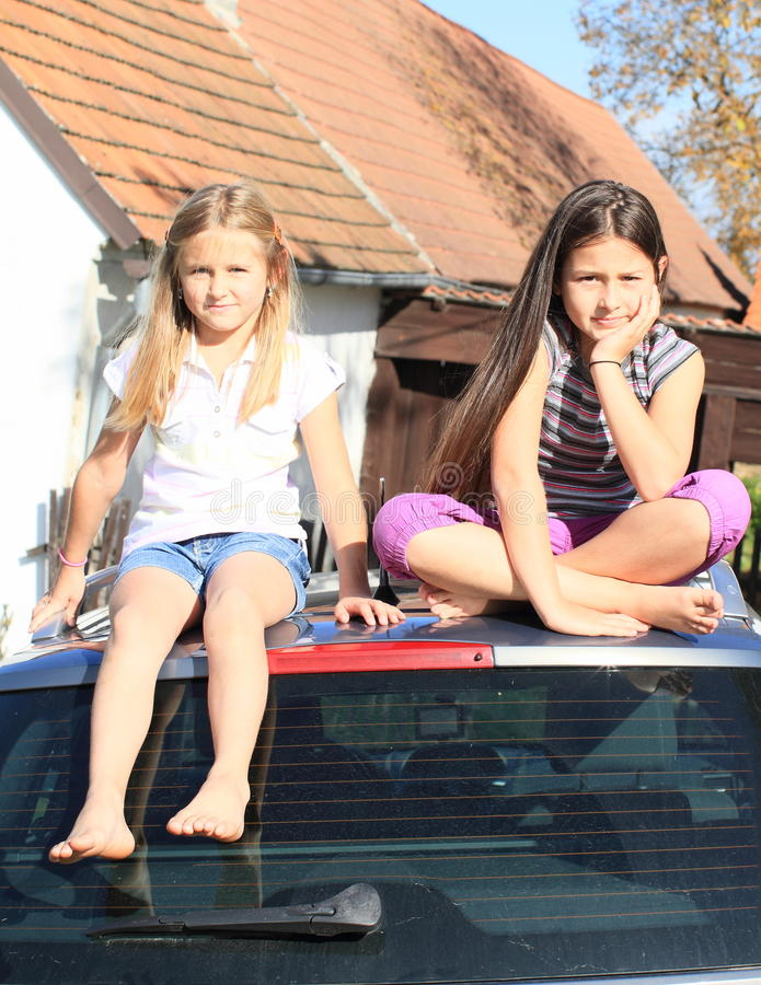 Little girls on a car stock photography