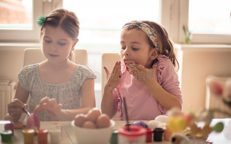 Fun on Easter. Little girls coloring Easter egg stock photos