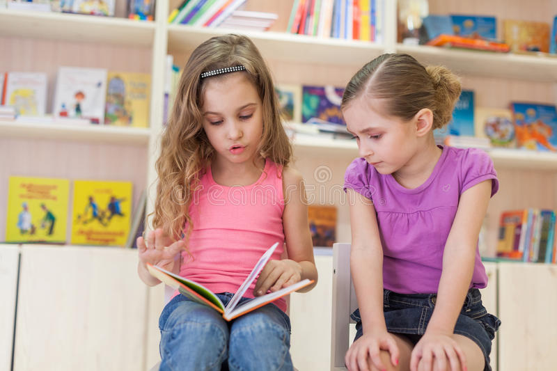 Little girls are concentrated in the library reading a book. Two little girls are concentrated in the library reading a book, focus on left girl stock photography