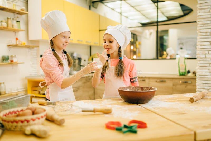 Little girls cooks in caps tastes vanilla powder stock images