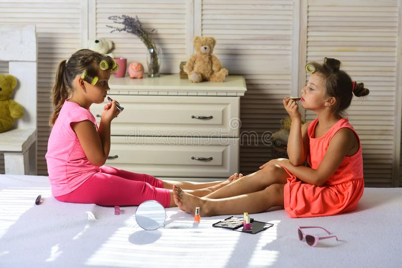 Little girls with curlers play with makeup accessories. Girls with serious faces do makeup in room with toys. Beauty and fashion concept. Children sit on bed royalty free stock photo