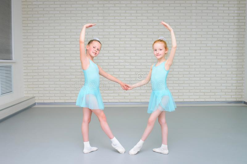 Little girls dancing ballet in studio. Young ballerinas gracefully posing at dance school, copy space. Little girls dancing ballet in studio. Young ballerinas royalty free stock photography