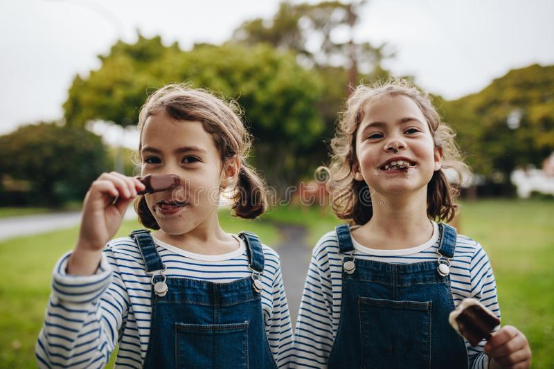 Little girls with a dirty mouth while eating ice cream royalty free stock image