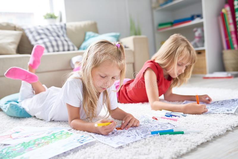 Little Girls Drawing on Floor stock image