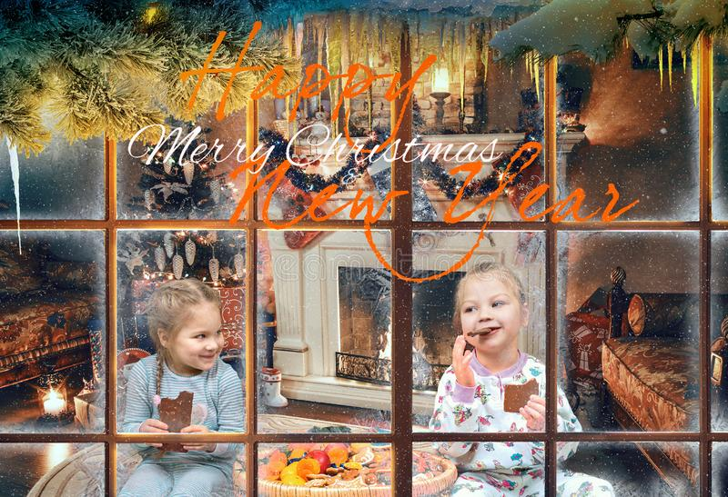 Little girls eat chocolate in the Christmas living room. Panorama of the Christmas living room - children eat sweets sitting on the floor near the fireplace stock photos