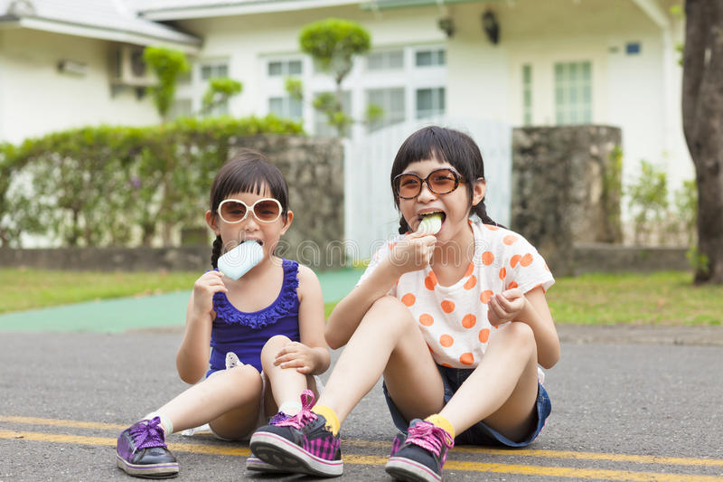 Little Girls Eating Ice Cream and sitting before their house royalty free stock image