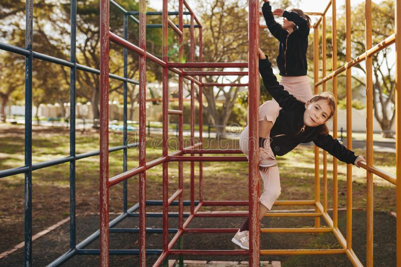 Little girls enjoying climbing on metal structure at playground royalty free stock photography
