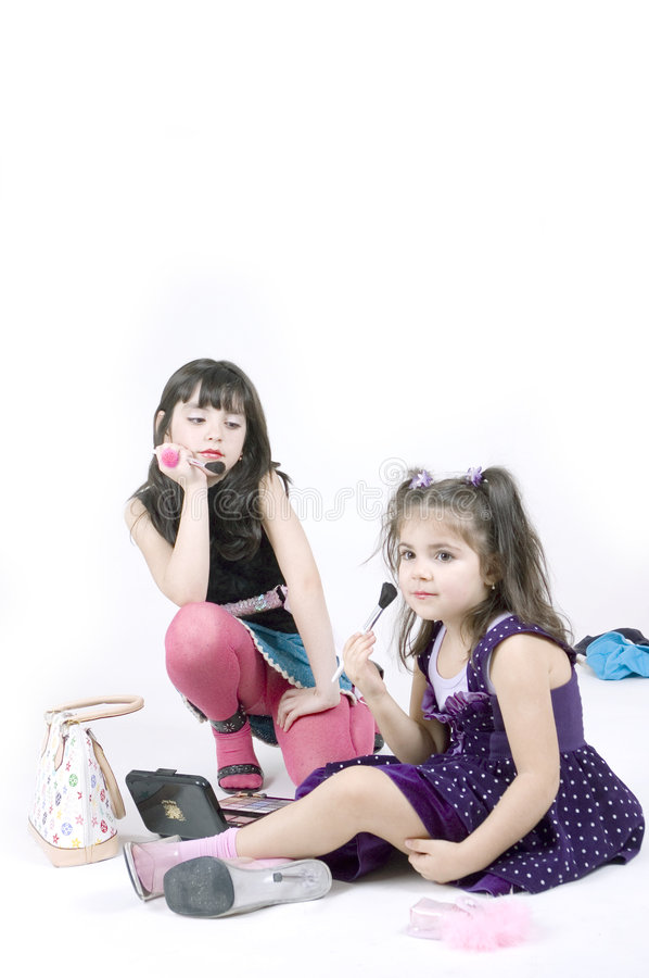 Little girls grown up. Two little girls with high heel shoes and make up items royalty free stock photo