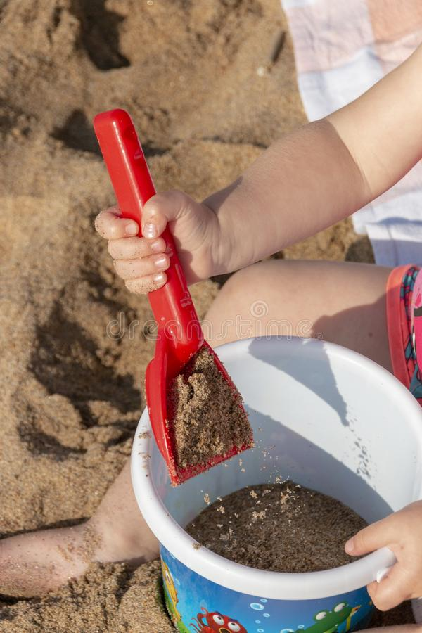 A Little girls hands. A close up view of a little girls hand with her spade and bucket playing with the beach sand on a beautiful summers day royalty free stock photos