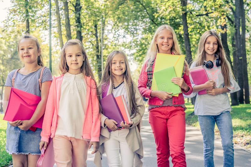 Little girls holding notebooks and folders. Little smiling blond girls holding colorful notebooks and folders royalty free stock photos