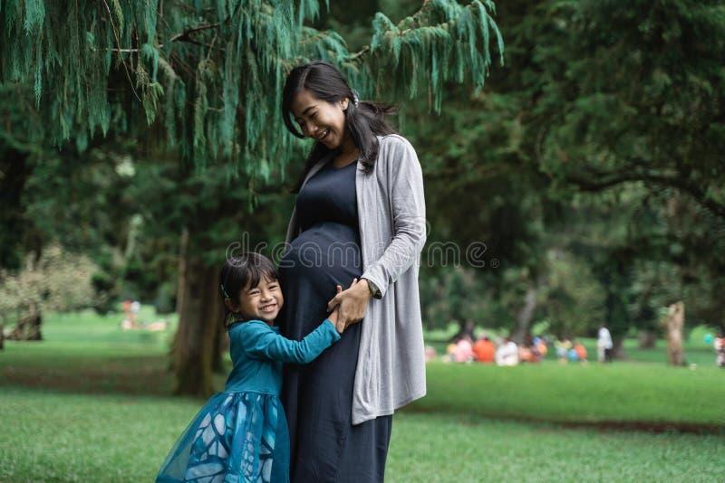Little girl hugs her pregnant mother stock photos