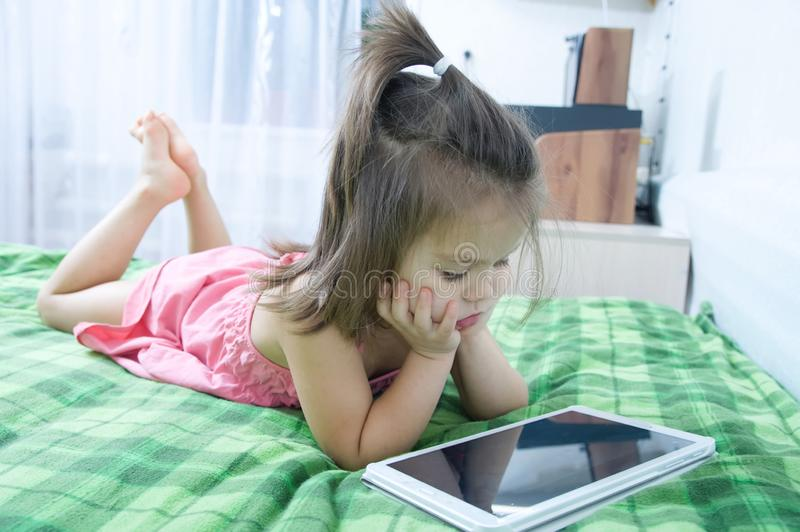 Little girls looking on pad lying on bed. Children time spending. Kids using tablet computer stock photos