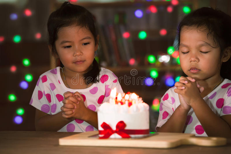 Little girls make folded hand to wish the good things for their birthday stock photo