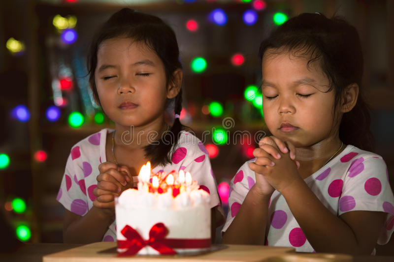 Little girls make folded hand to wish the good things for their birthday. Happy twin two asian little girls make folded hand to wish the good things for their stock image
