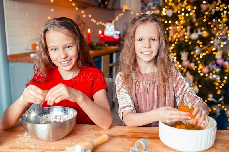 Little girls making Christmas gingerbread house at fireplace in decorated living room. Adorable little girls baking cookies background of lights and Christmas stock photo