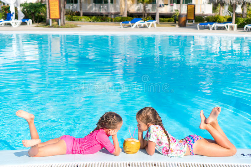 Little girls in outdoor swimming pool drink coconut milk. Adorable little girls playing in outdoor swimming pool royalty free stock photography