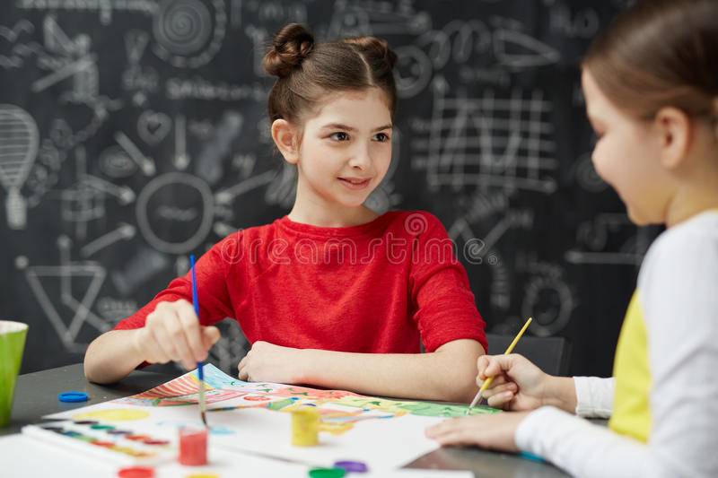 Little Girls Painting in Art Class. Portrait of pretty little girl painting pictures with friend during art lesson in school sitting against blackboard stock photos