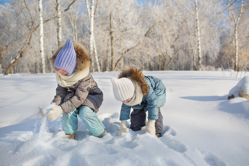 Little girls play with snow in a park in winter. Little girls play with snow in park in winter stock photos