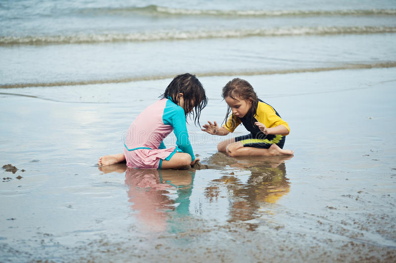 Little girls playing on the beach, family beach vacation. The Little girls playing on the beach, family beach vacation royalty free stock images
