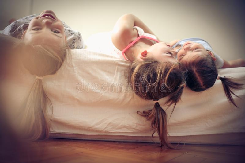 Fun n bed. Little girls playing in bed. Space for copy stock image