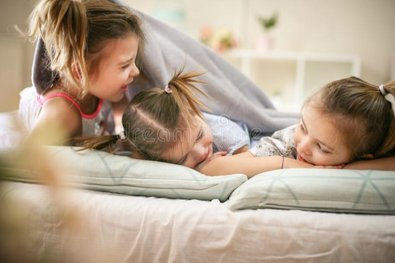 Funny morning. Little girls playing in bed. Space for copy royalty free stock photos