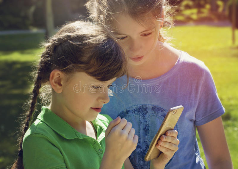 Little girls playing with phone royalty free stock images