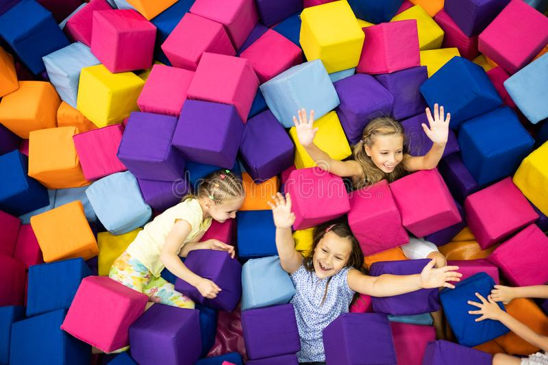 Little girls in the playroom. Little smiling girls and joyfully playing with colorful soft cubes in the playroom stock photos