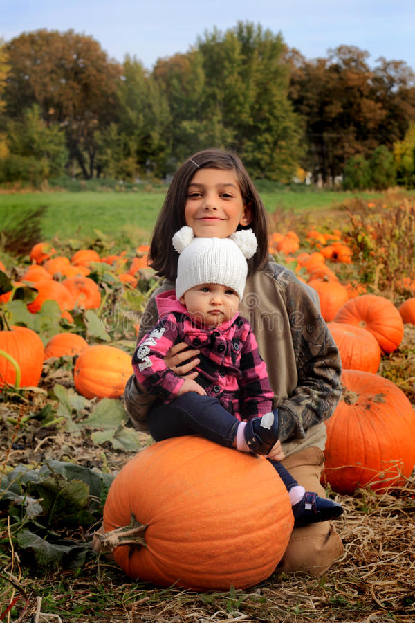 Little girls in pumpkin patch royalty free stock image