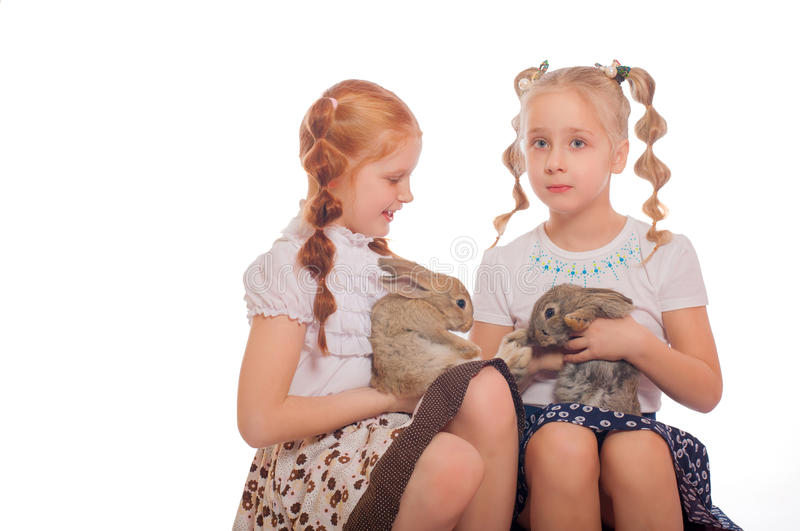 Little girls with rabbits in hands. Little girls with white rabbits in hands royalty free stock photography