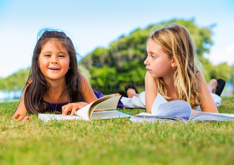 Little Girls Reading Books on Grass stock images