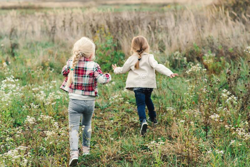Little girls running through a meadow. Adorable sisters having fun on a nature. Two little girlfriends. Happy and healthy royalty free stock images