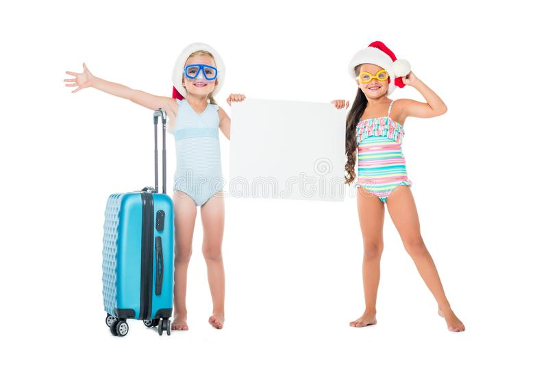 little girls in santa hats holding blank banner while standing with suitcase stock photos