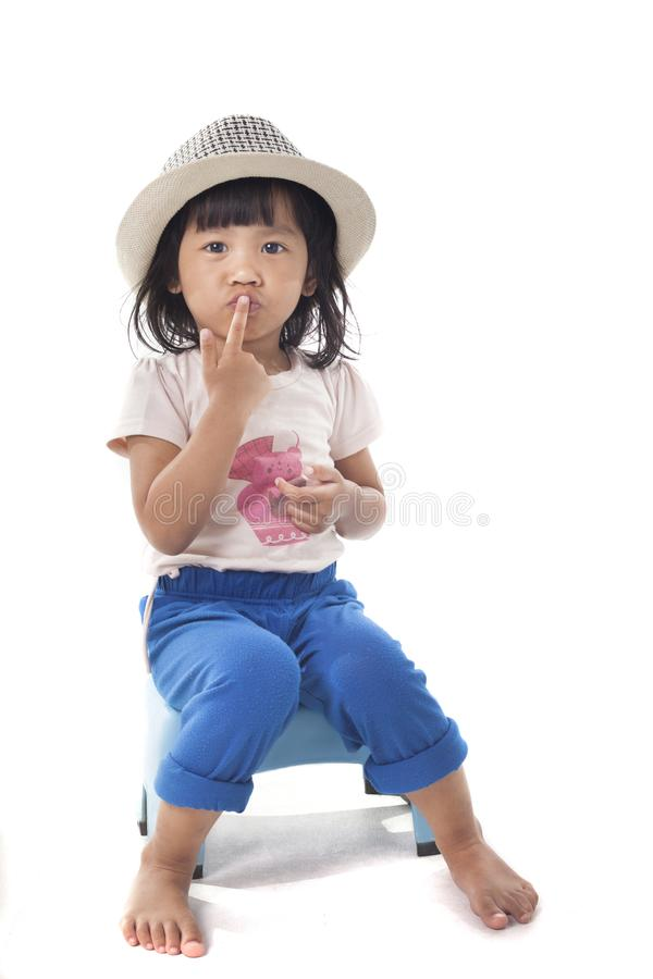 Little Girls Sitting and Covering Mouth. Portrait of beautiful little girl sitting and covering her mouth isolated on white indonesian malaysian thai asian shy royalty free stock photo