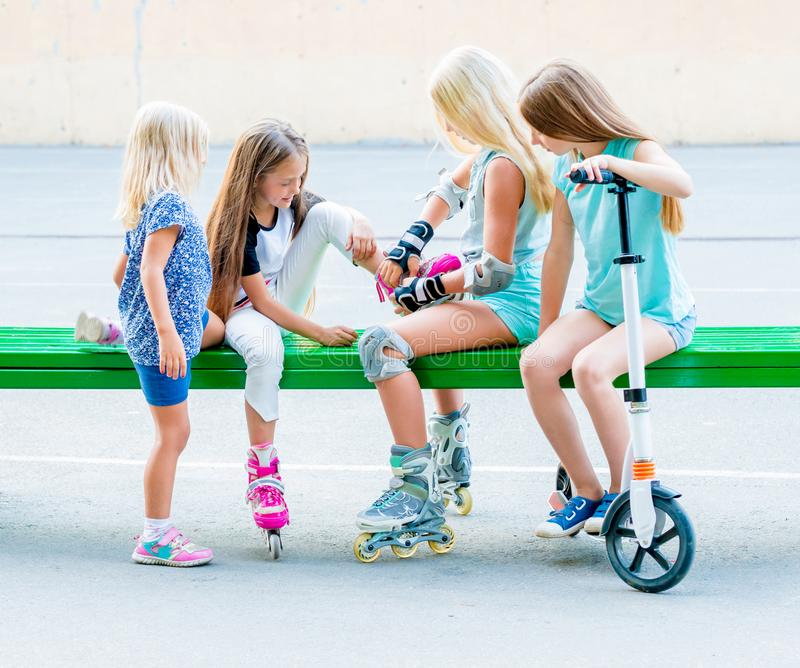 Little girls putting on rollerskates royalty free stock image