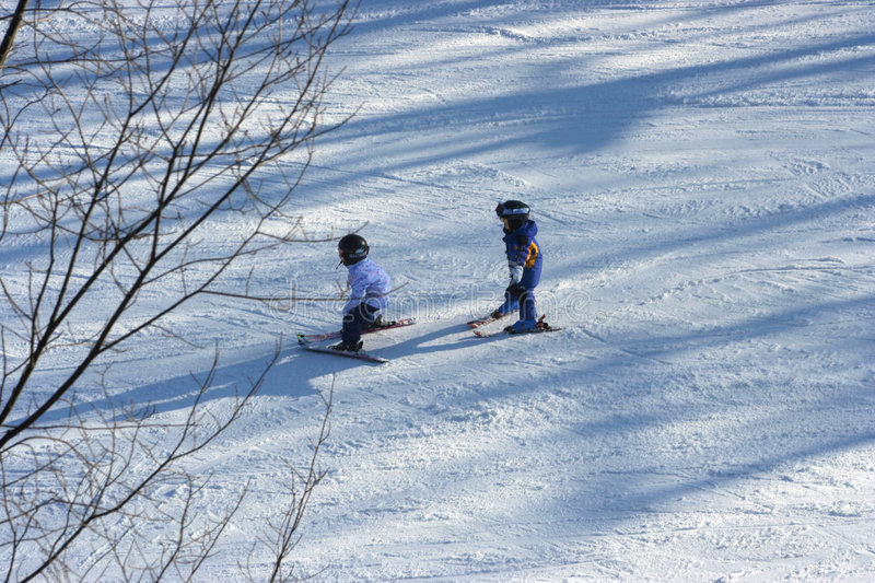 Little girls skiing. Little girlssnow ploughing down a hill skiing stock photography