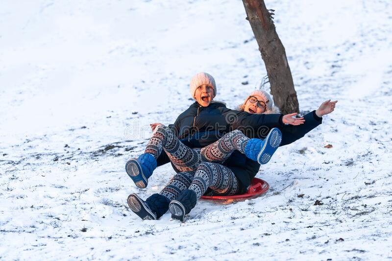 Little girls sliding from the hill in winter stock photo