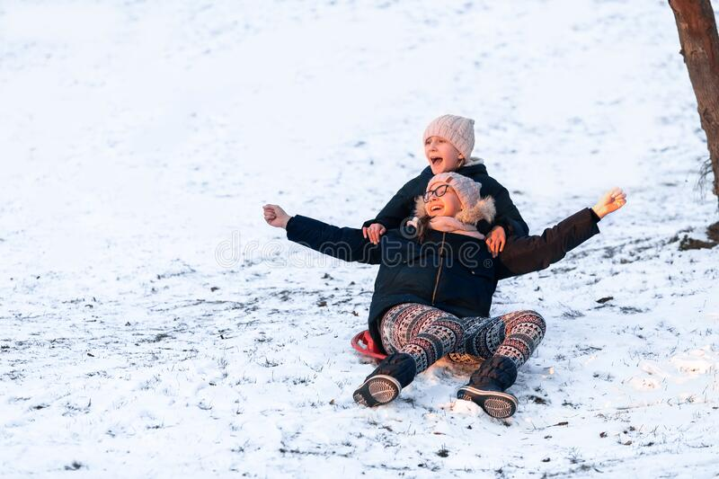 Little girls sliding from the hill in winter royalty free stock photos