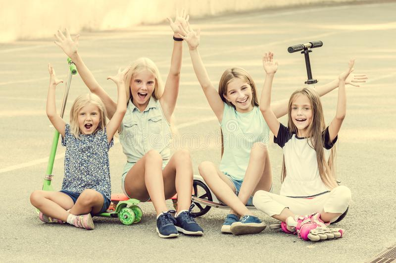 Little girls smiling sitting on the ground with raised hands royalty free stock photo