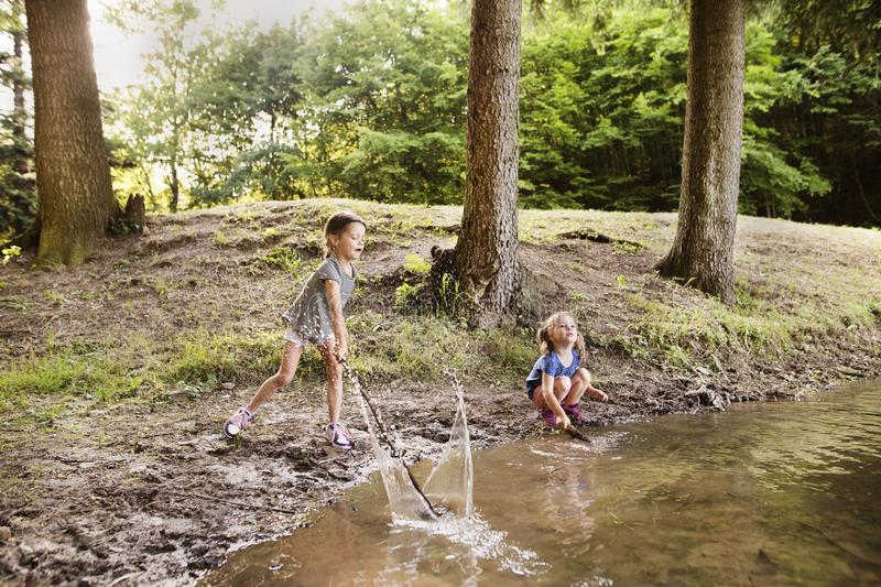 Little girls standing in the lake. Sunny summer. royalty free stock photography