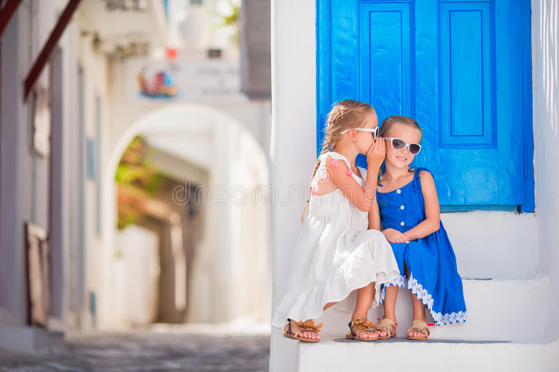 Little girls at street of typical greek traditional village on Mykonos Island, in Greece. Girl in blue dresses having fun outdoors on Mykonos streets royalty free stock photography