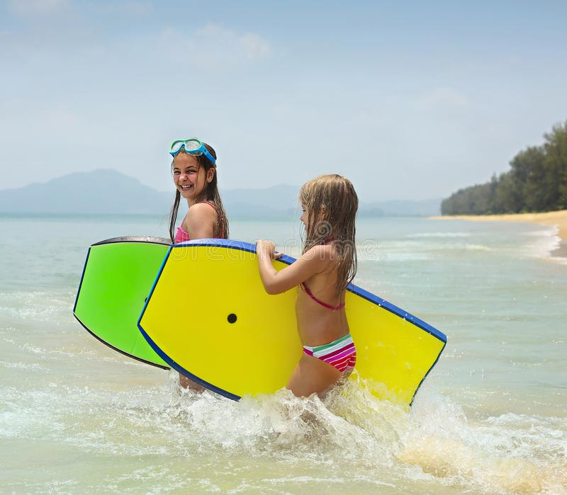 Little girls with surfing boards playing on tropical ocean beach. Summer water fun for surfer kids stock photos