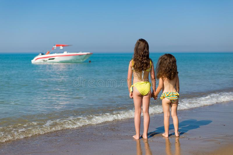 Little girls in swimsuits on the beach standing back and looking at the boat in the sea Children on vacation stock image