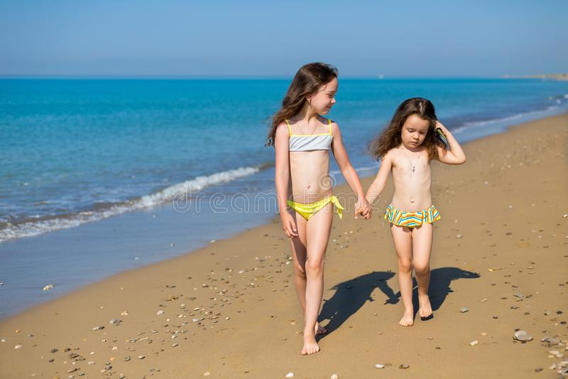 Little girls in swimsuits on the beach walking, holding hands. Children on vacation. Family vacation. happy sisters.  royalty free stock images
