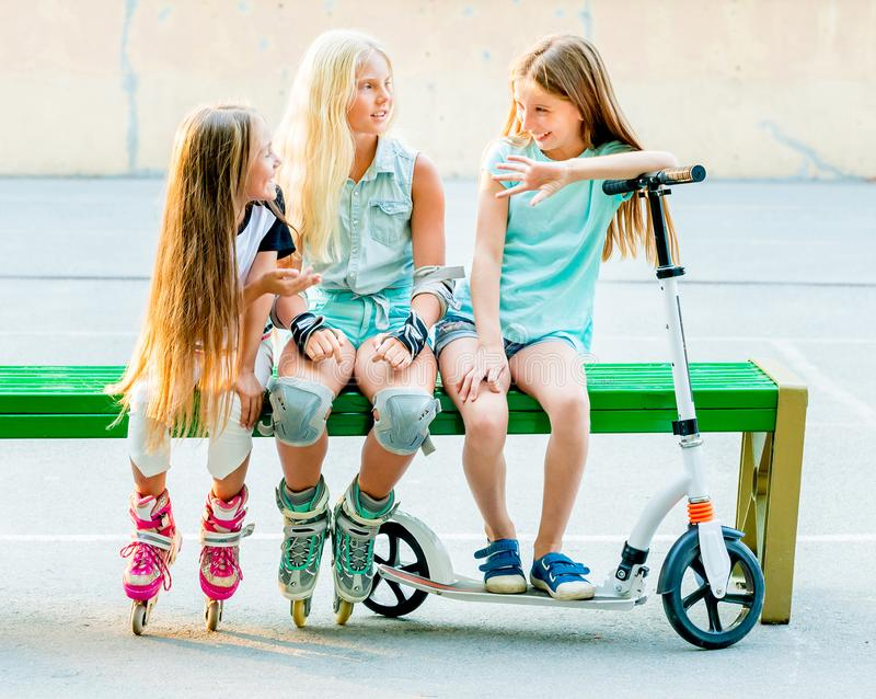 Little girls talk sitting on the green bench royalty free stock images