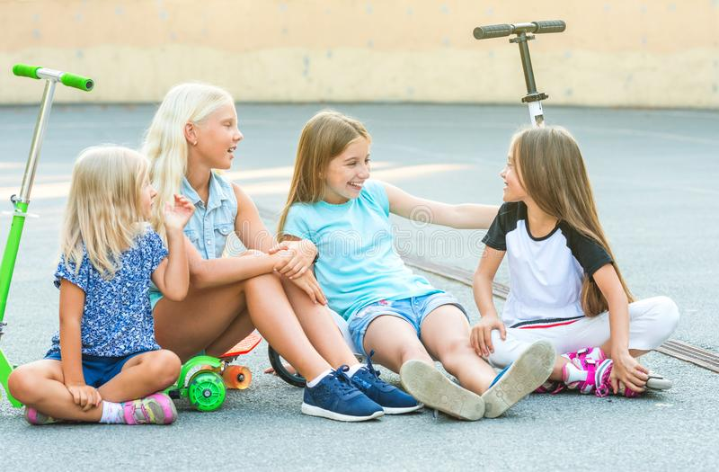 Little girls talk sitting on the ground royalty free stock photos